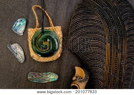 New Zealand - Maori themed objects - carved wooden mere greenstone and woven kite bag with shells on gray stone background - dark low key lighting theme stock photo