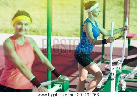 Two Active Caucasian Females In Good Fit Doing Outdoor Workout. One Athlete Looking Straight To Viewer and Intentionally Out of Focus. Horizontal Image stock photo