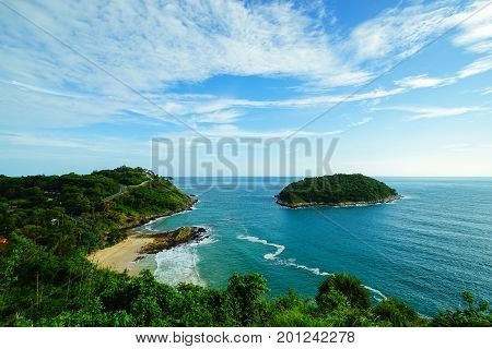 Panoramic view at windmill viewpoint. It overlooks Yanui Beach with beautiful sandy beaches and Promthep Cape. The wide blue cloudy sky and the blue sea are visible.There is small island far away stock photo