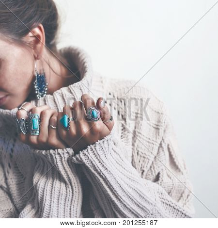 Boho jewelry on model: ethnic stone rings and earrings. Beautiful woman wearing warm woolen sweater and fashion jewellery. Minimal style and pastel tone. stock photo