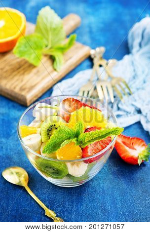 fruit salad in glass bowl and on a table stock photo