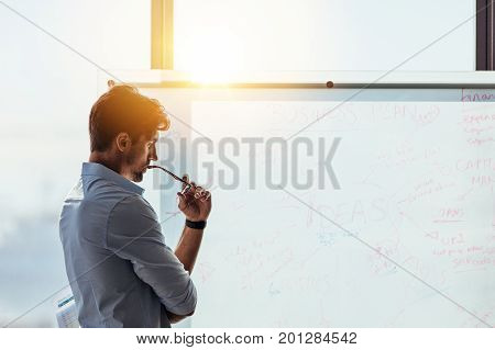 Business investor in deep thought looking at the business ideas written on the whiteboard. Businessman thinking while holding his spectacles to mouth
