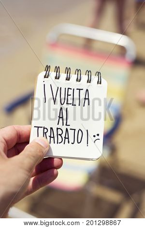 closeup of a young man in the beach showing a spiral notepad with the text vuelta al trabajo, back to work in Spanish in front of a deck chair in the seashore stock photo