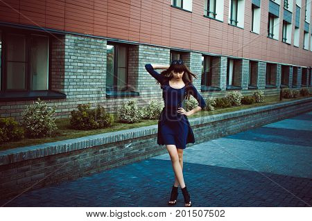 Young attractive woman with long legs with long hair in a blue elegant dress with a sword belt strolls in a European modern courtyard a warm summer day stock photo