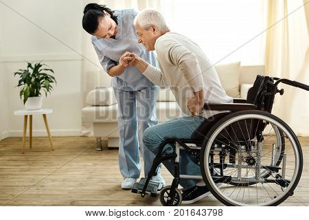 Physical disability. Nice sad aged man holding a caregivers hand and trying to get up while having a physical disability