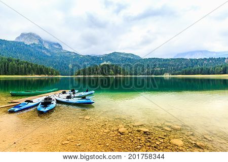 Kayaks boats docked on the shore of Black Lake. Mountain landscape at cloudy daytime, Durmitor National Park, Zabljak, Montenegro. Beautiful nature. Summer recreations, travel and vacation.