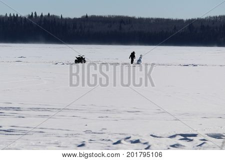 Checking Out a Lonely Snowman in the Middle of a Frozen Lake. stock photo