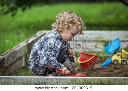 Young caucasianboy with curly hair playing in sandbox. Baby digging in sand. stock photo