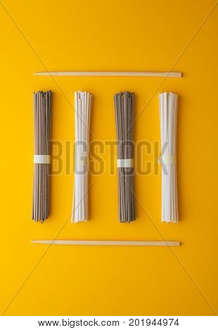 Flat lay Asian soba noodles and udon and chopsticks on a bright yellow background. Minimalism. stock photo