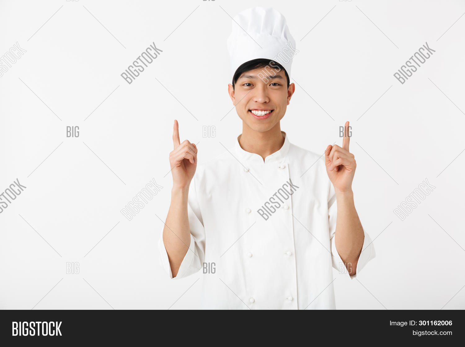 Excited asian chef wearing uniform standing isolated over white background, pointing at copy space