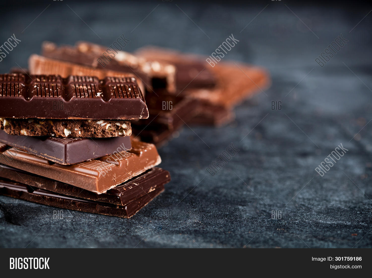 Chunks of broken chocolate stacked on black board. Chocolate bars pieces stack on black background. Sweet food photo concept with copy space.