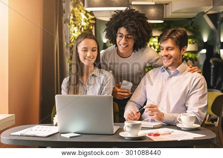 Brainstorm. Millennial business team discussing ideas for project in cafe, looking at laptop together, free space stock photo