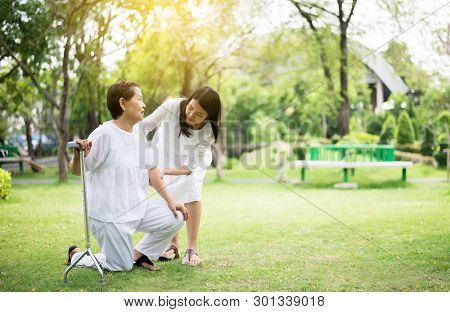 Elderly asian woman falling while walking to do physical with stick at park,Caretaker take care and support,Physical therapy stock photo