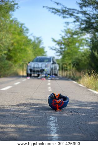 Close-up of a bicycling helmet fallen on the asphalt next to a bicycle after car accident on the street stock photo