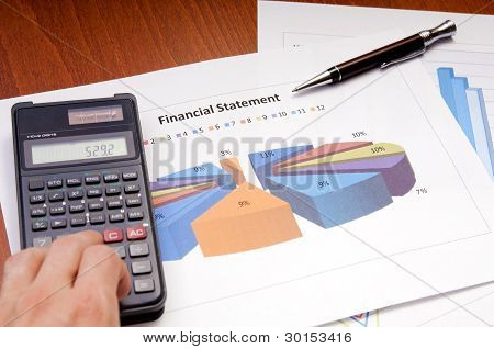 Graphs calculator and paper statements for finance concept stock photo