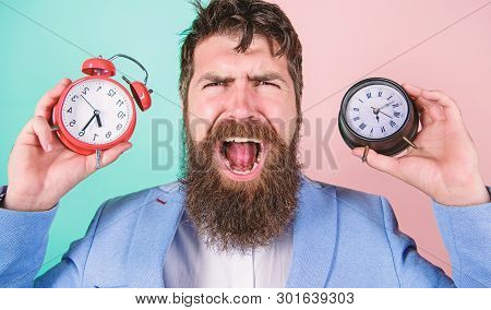 Changing time zones affect health. Does changing clock mess with your health. Man bearded hipster hold two different clocks. Guy unshaven puzzled face having problems with changing time. Time zone stock photo