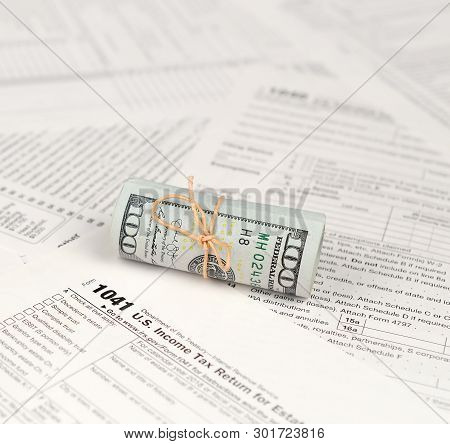 1041 U.S. Income tax return for Estates and Trusts form with roll of american dollar banknotes stock photo