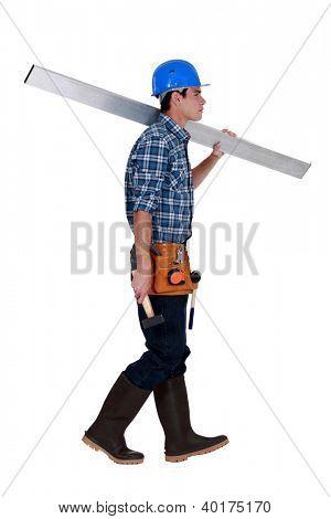 Man carrying metal beam stock photo