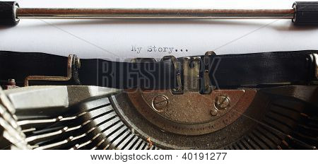 A Closeup image of the typebars and ribbon of an old style typewriter and paper with the text: My Story... (Shallow Depth of Field) in a panorama crop stock photo