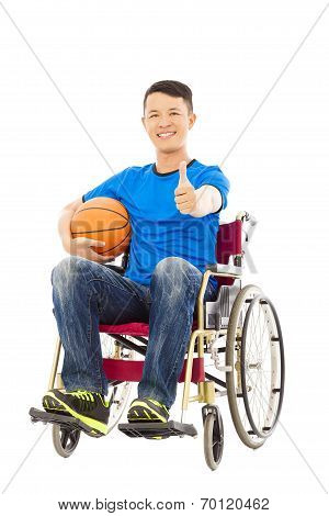 asia young man sitting on a wheelchair and thumb up with a basketball stock photo