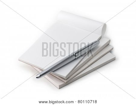 Stack of blank memo pads in real use condition, with a silver pen, isolated on white.  stock photo