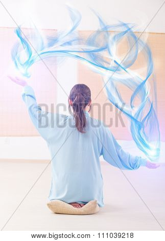 Beautiful woman doing qi gong tai chi exercise or reiki wearing professional, original Chinese clothes at gym stock photo