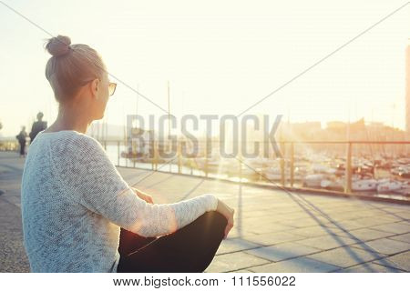 Female looking at the landscape while sitting near sea port