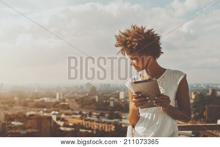 Cheerful young black curly female leaning on railing of balcony of skyscraper holding digital tablet and looking down on city from high above; with copy space place for text your message or advert. stock photo