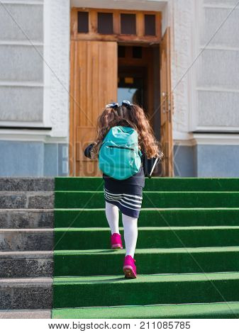 The girl goes to school with a briefcase and a book on the steps behind the back