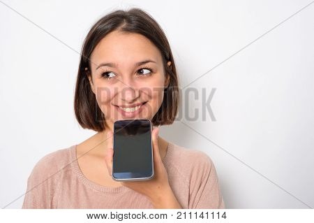 Young woman using phone vocal assistant and sending vocal message stock photo