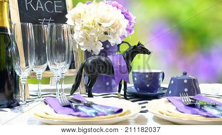 Horse racing Racing Day Luncheon fine dining table setting with small black fascinator hat decorations and champagne with copy space. stock photo