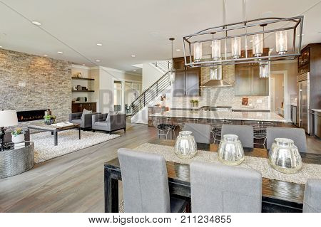 Open plan kitchen equipped with high-end appliances opens to the dining room and the great room with a floor to ceiling stone fireplace. Northwest USA stock photo