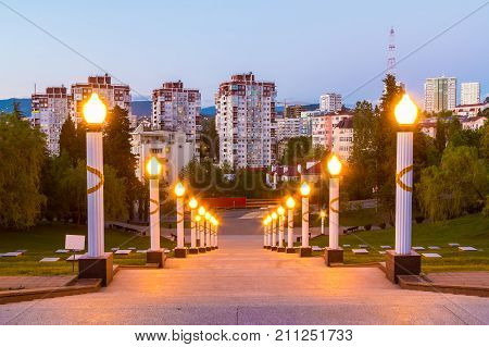Stairs and luminous lampposts of Zavokzalnyy Memorial Complex on the background of apartment buildings at twilight Sochi Russia stock photo
