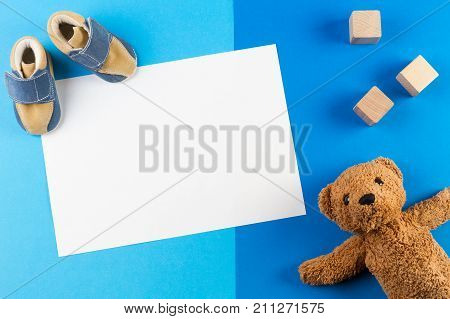 Its a boy, blue theme Baby shower or Nursery background with blank card, teddy besr, wooden blocks and baby shoes on blue background stock photo