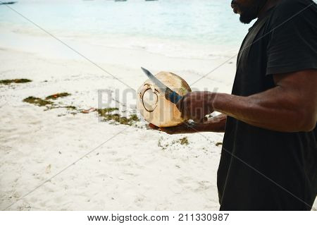 African man peels coconut on the beach stock photo
