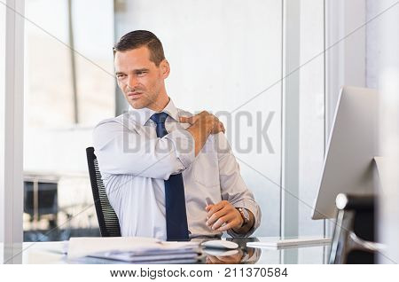 Young businessman at work suffering from shoulder pain. Businessman holding shoulder and stretching after completion of work. Stressed businessman have back pain after long hours of work. stock photo