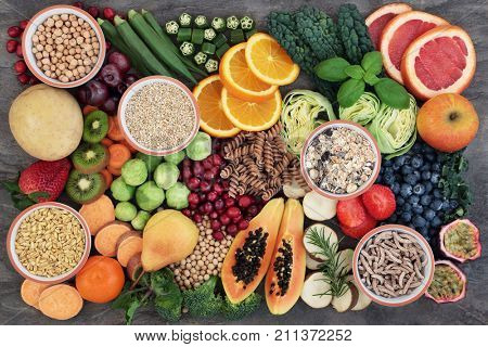 Health food concept for a high fiber diet with fruit, vegetables, cereals, whole wheat pasta, grains