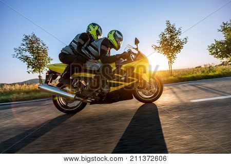 Motorbikers on sports motorbike riding in sunset. Outdoor photography, European landscape. Travel and sport photography. Motorbike is manufactured and designed in Japan stock photo
