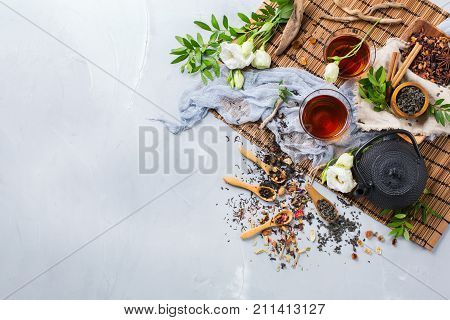 Food and drink still life concept. Selection assortment of different japanese chinese herbal masala tea infusion beverage teapot with white flowers on the table. Top view copy space background stock photo