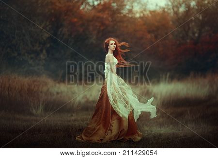 Beautiful young woman with very long red hair in a golden medieval dress walking through the autumn forest. Long red hair develops in the wind. Creative colors and Artistic processing.