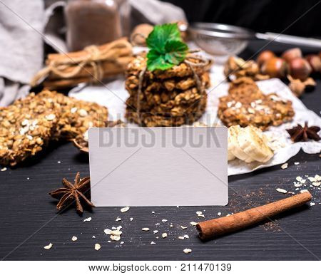 empty white paper tag on a black wooden table and oatmeal cookies and ingredients