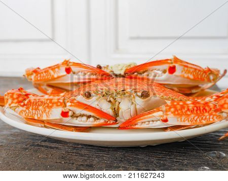 orange boiled crab in the plate on wood surface stock photo