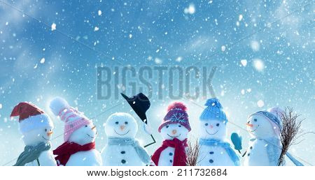 Merry Christmas and happy New Year greeting card with copy-space.Many snowmen standing in winter Chr