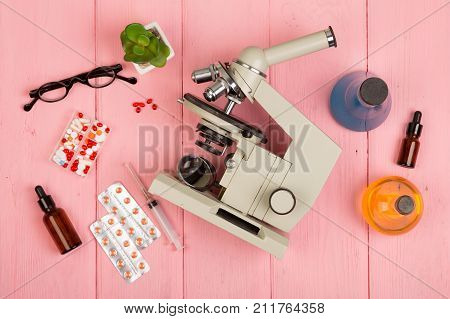 Workplace scientist / doctor - microscope pills syringe eyeglasses chemical flasks with liquid on pink wooden table stock photo