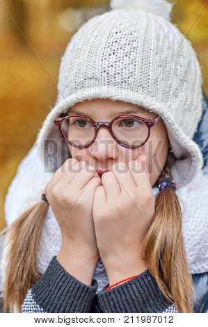 portrait of teenage girl in glasses, blowing on her hands to keep warm in the cold stock photo