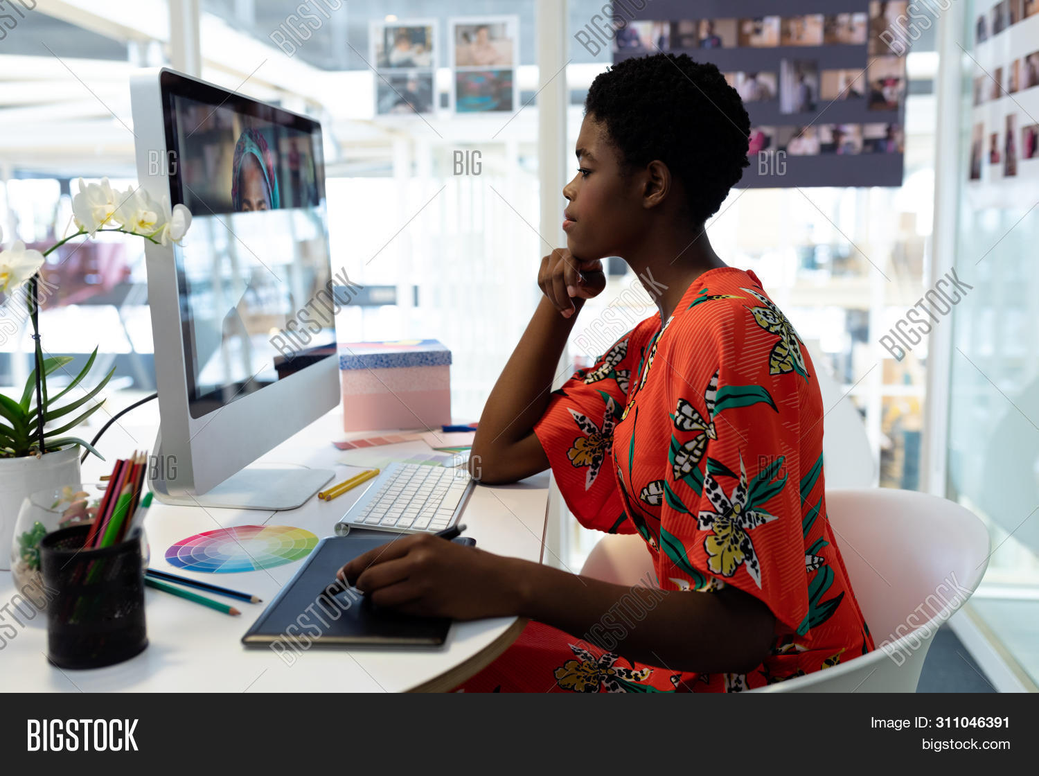 Side view of beautiful young African American female graphic designer using graphic tablet at desk i