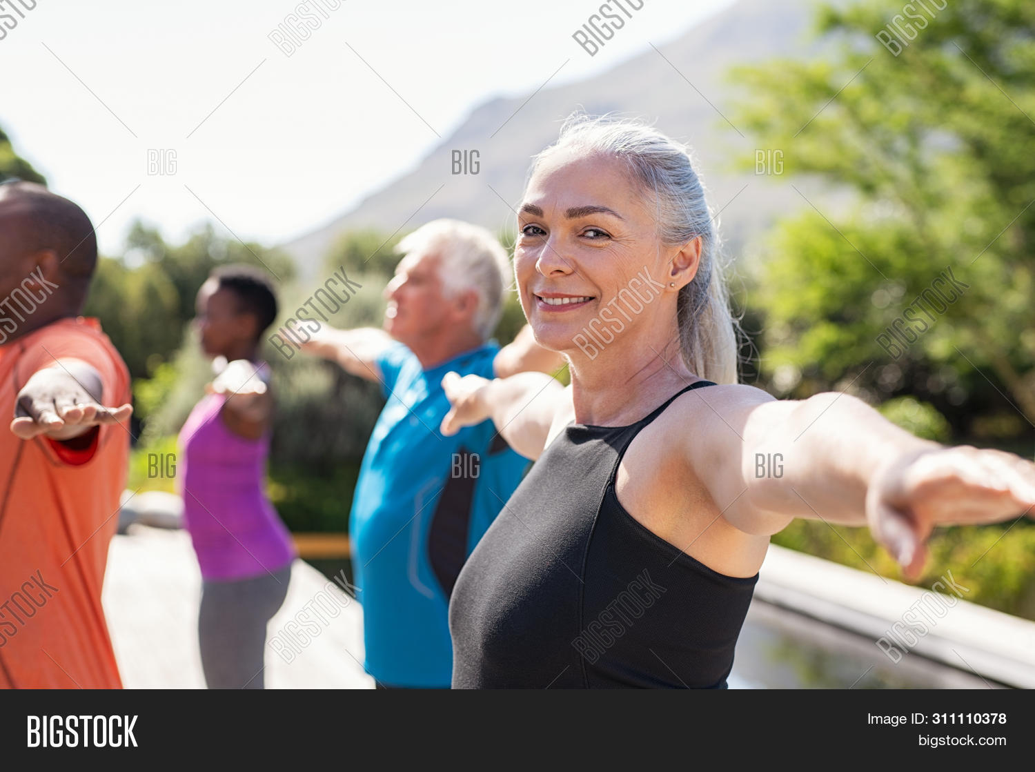 Portrait of happy senior woman practicing yoga outdoor with fitness class. Beautiful mature woman st