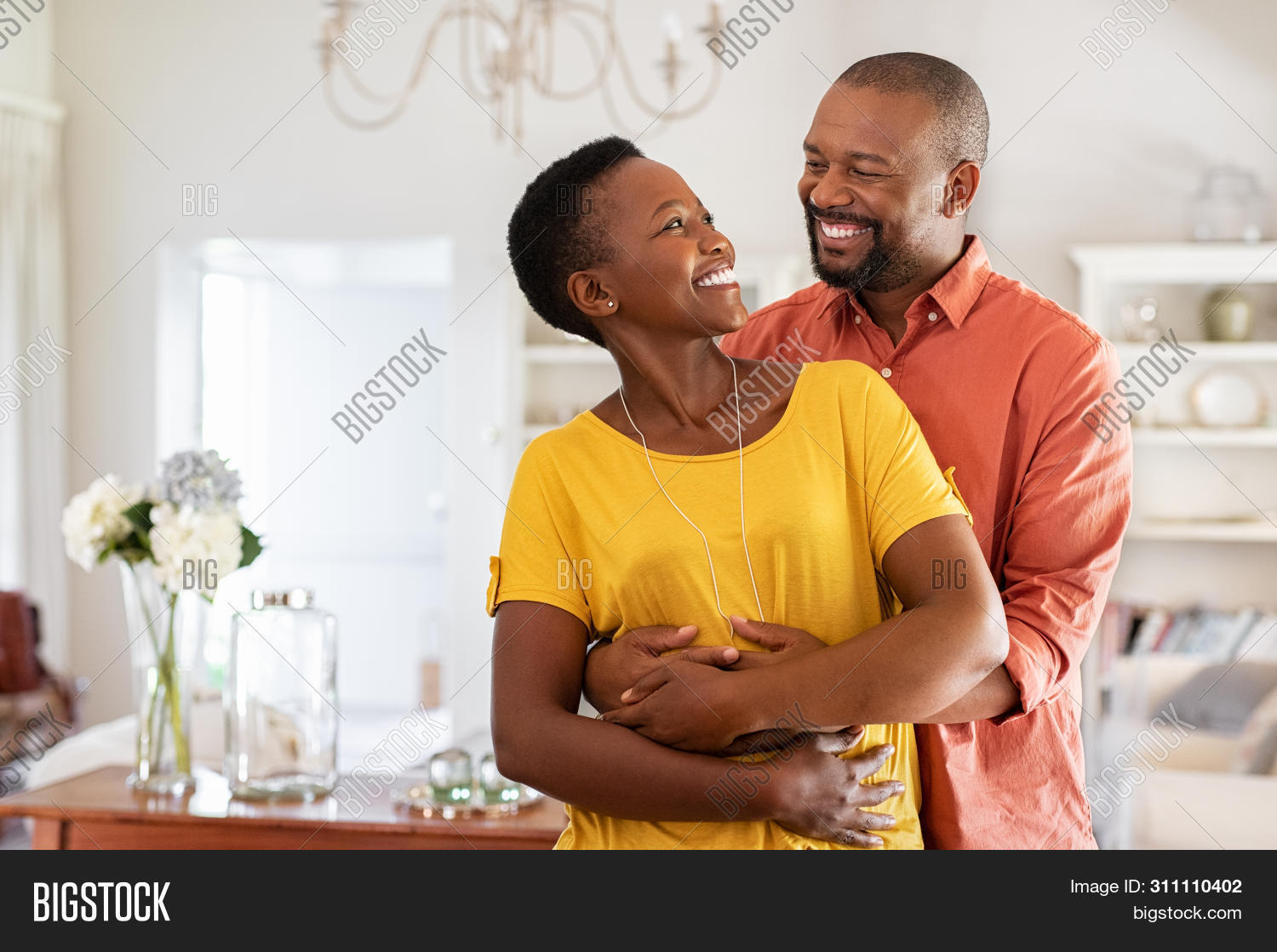 affection,african,american,beautiful,black,bonding,boyfriend,casual,celebration,cheerful,copy space,couple in love,embrace,embracing,fall in love,from behind,future,girlfriend,happy,home,hug,hugging couple,husband,indoors,laughing couple,looking at each other,love,loving family,man,married,mature,mid adult man,mid adult woman,middle aged couple,middle aged man,middle aged woman,newly married,relationship,romance,romantic,romantic man,smile,standing,together,toothy smile,wife,woman