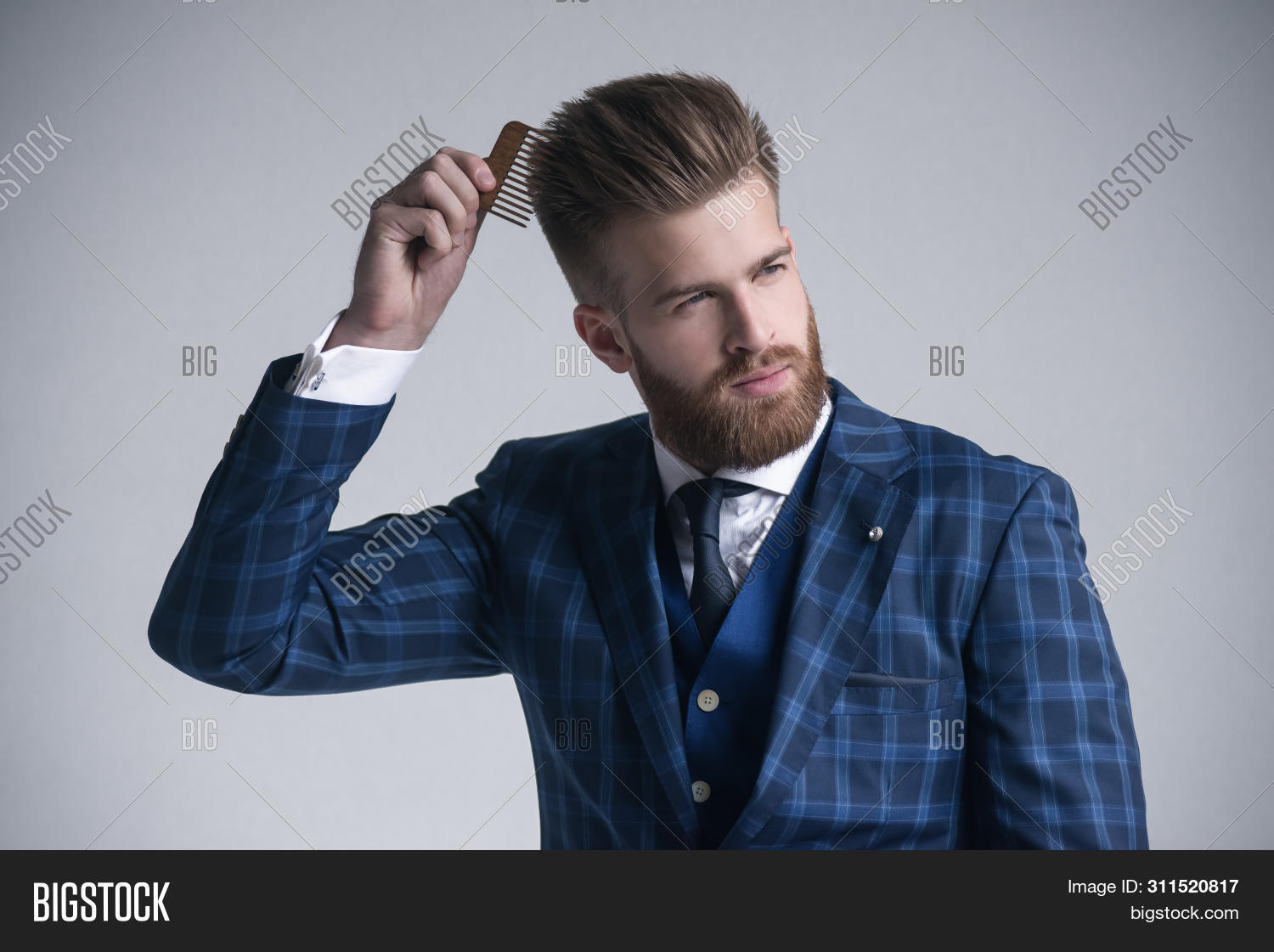 Confident In His Perfect Style. Confident Young Bearded Man Combing His Hair And Looking At Away Whi