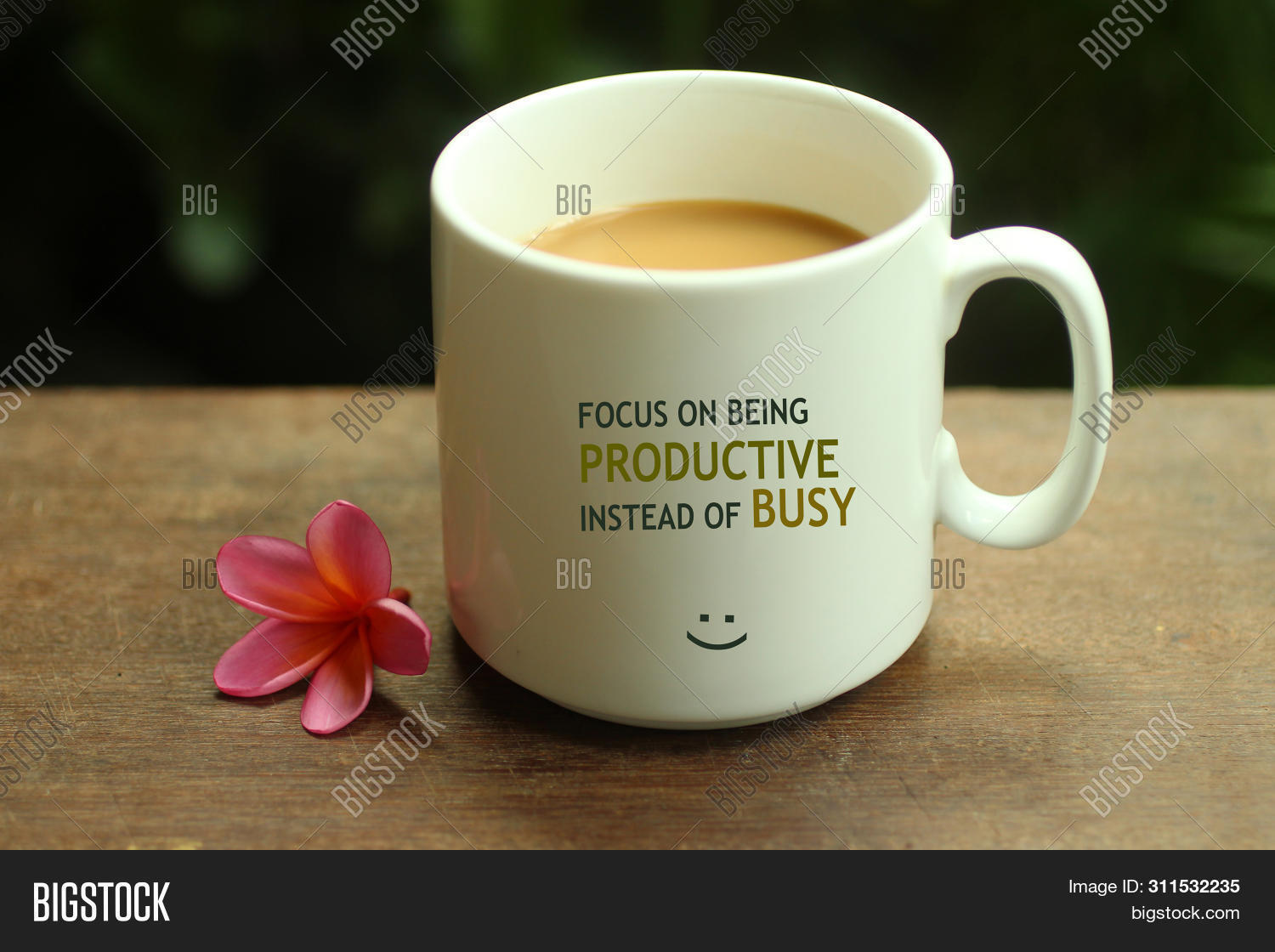 Morning Coffee concept. Work inspirational quote on a mug - Focus on being productive instead of busy. With white mug of coffee and self notes reminder on it. Morning tea or coffee concept with mug & a smile face sign and a beautiful pink Bali frangipani.